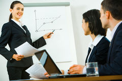Business briefing. Portrait of confident woman demonstrating her report to colleagues royalty free stock photography