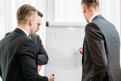 Business briefing visualization flip chart office. Business briefing and goals visualization. company managers writing on the flip chart in office board room Stock Image