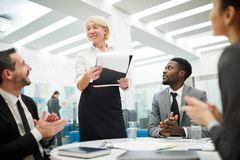Business Briefing. Multi-ethnic group of people sitting at table during meeting in office, focus on mature businesswoman giving presentation stock image