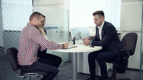 Business broker having a meeting with clients. 4K business broker, consultant, insurance agent or salesman having a meeting with clients in his office looking up stock images