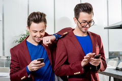 Business brothers twins with phones Royalty Free Stock Images