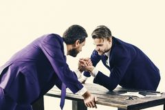 Business brouken. Men in suit or businessmen with serious face compete. In armwrestling on table on white background. Businessmen fighting for leadership Stock Photo