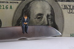 Business Budget Cut. Miniature businessman sitting on edge of knife Royalty Free Stock Image