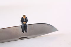 Business Budget Cut Concept. Miniature businessman sitting on edge of knife Royalty Free Stock Images