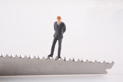 Business Budget Cut Concept. Miniature businessman sitting on edge of knife Stock Images