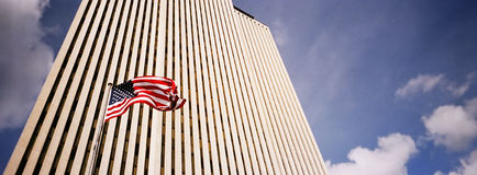Business Building. Reaching to the sky with an American flag in front of it waving Royalty Free Stock Images