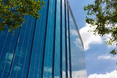 Business building reflecting clouds and blue sky. Business building with many glass windows reflecting sky on clear day Royalty Free Stock Photos