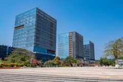 Business buildings with glass exterior and plaza with trees on blue sky background stock photos