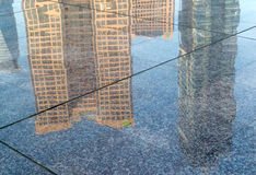 Business buildings reflected in the street Stock Photos