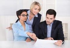 business businessman cmputer desk laptop meeting smiling talking to using woman Τρεις άνθρωποι που κάθονται στον πίνακα σε ένα γρ στοκ εικόνα