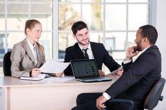 business businessman cmputer desk laptop meeting smiling talking to using woman Τρεις επιτυχείς επιχειρηματίες που κάθονται στο θ Στοκ Εικόνα