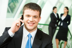 Business call. Portrait of a young successful businessman making business call on mobile looking at camera on the background of two standing women Stock Photography