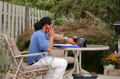 Business Call. A professional working outside from his home making business calls on his cell phone Royalty Free Stock Image