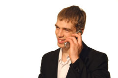 Business call - smile. Young businessman in black suit making a pleasant call on his cell phone smiling royalty free stock photos