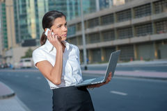 Business call. Successful businesswoman standing in the street i Royalty Free Stock Images