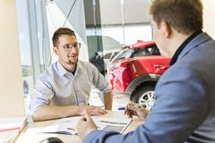 Business car seller working with the client. A Business car seller working with the client stock photos