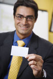 Business card. Work place: successful businessman smiling and holding a white card Stock Photos