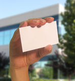 Business Card. A photo of a woman holding a business card with a business backdrop stock images