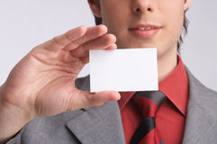 Business-card. Ambitious businessman in his grey suit holds a business-card in a hand, introducing and presenting his company, introduction - formal presentation Stock Image