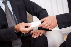 Business card being passed over Stock Images