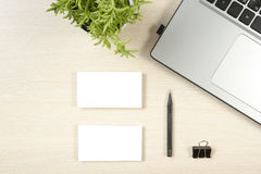 Business card blank, laptop, flower and pencil at office desk table top view. Corporate stationery branding mock-up.  Royalty Free Stock Photos