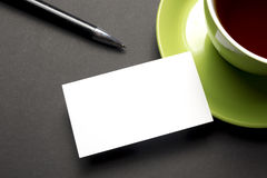 Business card blank over coffee cup and pen at office table. Corporate stationery branding mock-up Stock Images