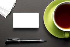Business card blank over coffee cup and pen at office table. Corporate stationery branding mock-up Stock Photo