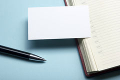 Business card blank over notepad at office table. Corporate stationery branding mock-up Stock Image