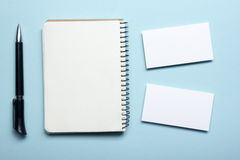 Business card blank over notepad at office table. Corporate stationery branding mock-up Stock Photos