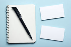 Business card blank over notepad at office table. Corporate stationery branding mock-up Royalty Free Stock Image