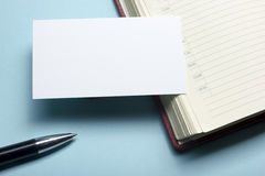 Business card blank over notepad at office table. Corporate stationery branding mock-up Stock Photo