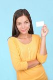 Business card casual woman. Sign woman showing a blank business card on blue background Stock Photography