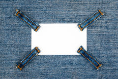 Business card with four straps jeans, lies on the light denim Royalty Free Stock Images