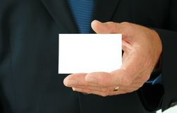 Business Card Hand. Business card being held by suited businessman royalty free stock photography