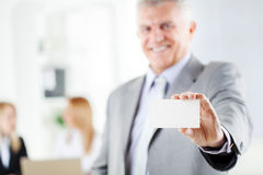 Business Card. Happy senior businessman holding Blank business card in the office. Looking at camera. Selective Focus Stock Photo