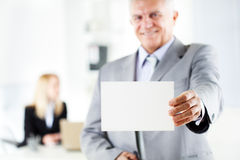 Business Card. Happy senior businessman holding Blank business card in the office. Looking at camera. Selective Focus. Focus on business card Royalty Free Stock Photo