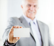 Business card. Happy senior businessman holding Blank business card. Selective Focus. Focus on business card Stock Photography