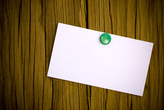 Business card for message. Business card and thumbtack on a wooden wall Royalty Free Stock Image