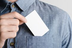 Free Business Card Mock-Up 85x55mm - Man In A Chambray Shirt Holding A Blank Card On A Gray Background Stock Photos - 187731183