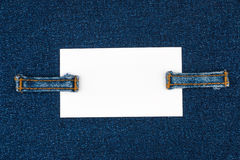 Business card with two straps  jeans, lies on the dark denim Royalty Free Stock Images