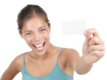 Business card woman. Business card or blank sign. Beautiful young woman with a very excited big smile showing a white business card / notecard. Shallow depth of Royalty Free Stock Photography