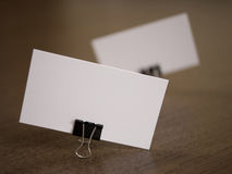 Business cards with clip fastener on a desk Royalty Free Stock Images