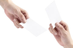 Business cards. Two hands exchanging blank bussiness cards on white background Royalty Free Stock Photo