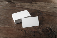 Business cards on wooden background. Photo of blank business cards with soft shadows on dark brown wooden background. Blank template for design presentations and Stock Images