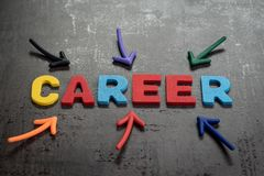 Business career path opportunities concept by colorful wooden al. Phabets as word CAREER with magnet arrows pointing on dark black chalkboard cement wall Stock Photography