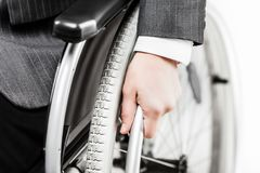 Invalid or disabled businessman in black suit sitting wheelchair stock photography