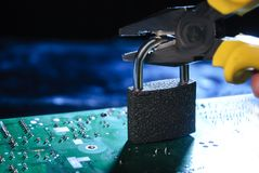 Hacking personal database concept. Pliers breaking the lock on the background of the computer board stock image