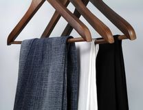 Business or casual?. Blue jeans and trousers on wooden hangers royalty free stock image