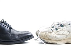 Business casual. Two pairs of shoes ? new business shoes and old tennis shoes Stock Photography