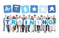 Business And Casual People Holding Cardboards. Multi-ethnic group of business and casual people holding cardboards forming training and related symbols above Stock Photos